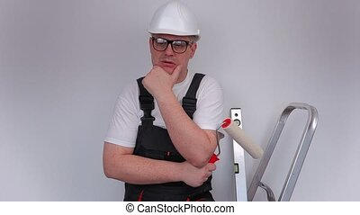Builder thinking and show thumb up near wall in apartment
