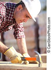Builder using a hammer