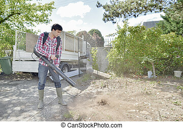 Builder using a leaf blower