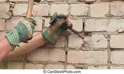 Builder using chisel and hammer near brick wall
