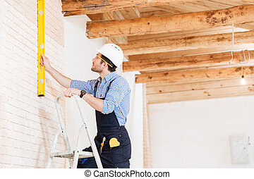 Builder using consruction level and standing n the ladder at...