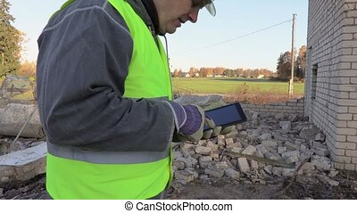 Builder using tablet and checking damaged bricks