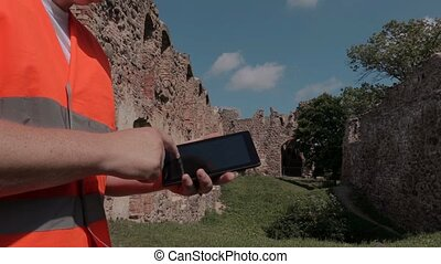 Builder using tablet in the castle yard