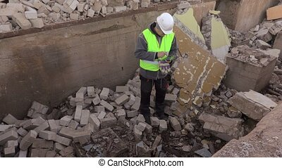 Builder using tablet PC on bricks ruins