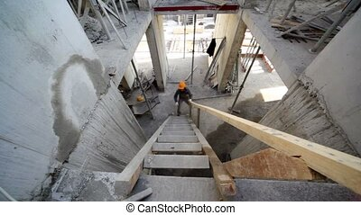 Builder walk up by wooden stairs on next floor, view from...