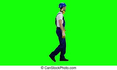 Builder walks and waves to his workers, showing a thumbs-up. Green screen. Side view