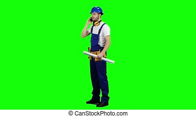 Builder with a drawing in his hands is talking on the phone. Green screen