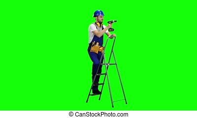 Builder with a drill in his hands climbs the stairs. Green screen