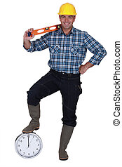 Builder with a spirit level and a clock