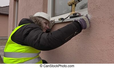 Builder with drill near window