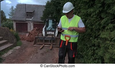 Builder with spade and tablet near tractor