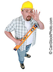 Builder with spirit-level holding hand to ear