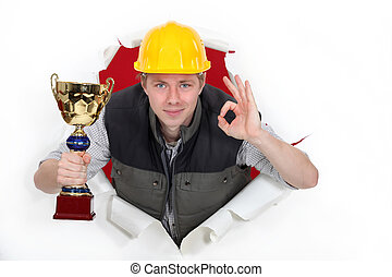 Builder with trophy making OK sign