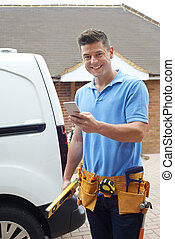 Builder With Van Checks Text Messages On Mobile Phone Outside House