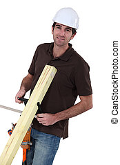 Builder with wood in a vice