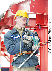 builder worker in safety protective equipment assembling metal construction frame with electric spanner tool