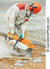 builder worker cutting curb with disc saw