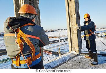 builder worker installing concrete panel - builder worker in...