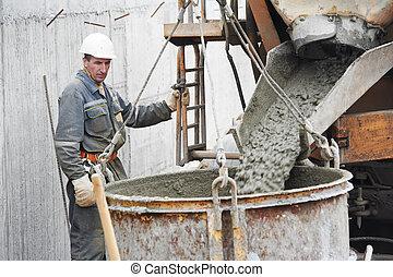 Builder worker pouring concrete into barrel - Builder worker...