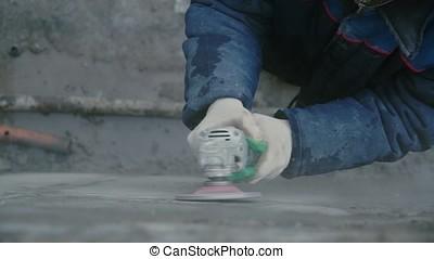 Builder worker with grinder machine cutting finishing...