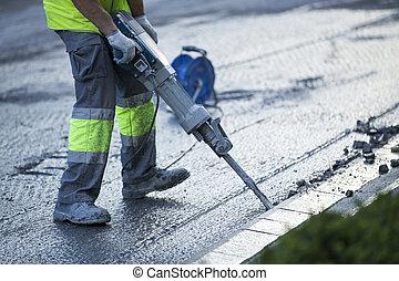 Builder worker with pneumatic hammer drill equipment...