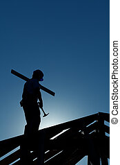 Builder working late on top of building holding hammer - in...