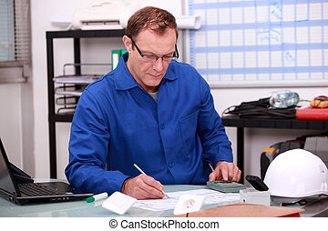 Builder working on paperwork in an office