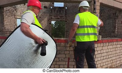 Builders are going to take photos on construction site