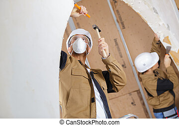 builders are using a chisel and hammer
