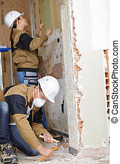 builders carving wall and floor of a house