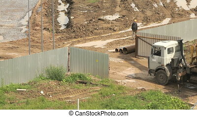 Builders going along a fence of construction site - Builders...