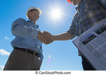 Builders Handshake, Architect And Contractor Agreement During Meeting Discussing Blueprint Buiding Plan On Construction Site