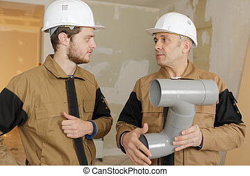 builders holding sewer pipes