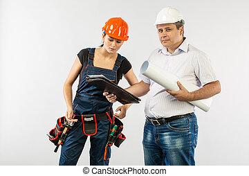 builders in hardhat or helmet discussing blueprints with tablet