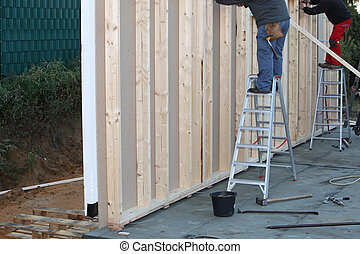 Builders installing a timber frame house - Builders standing...