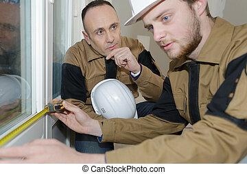 builders installing measuring windows