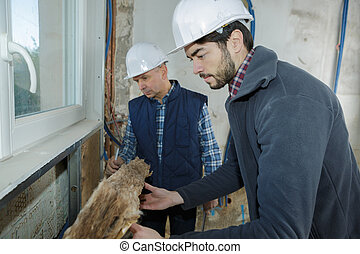 builders insulating wooden house with mineral rock wool