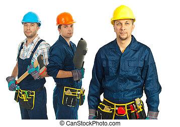 Builders men team - Mid adult builder man standing in front...