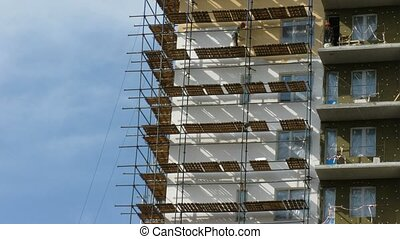 Builders paint the many-storeyed house. Time lapse.