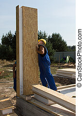 Builders positioning an upright wall panel
