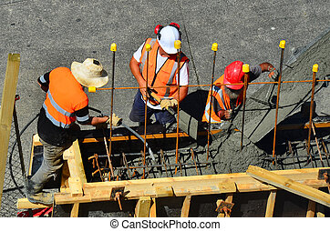 Builders pour cement to a concrete wall
