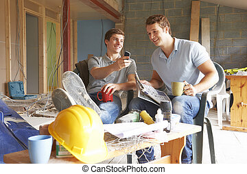 Builders Relaxing During Break On Site
