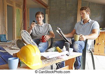 Builders Relaxing During Break On Site