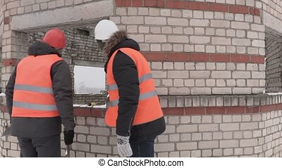 Builders talking near unfinished building