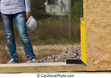 Builders try square or right angle being used on a construction site to ensure that a wooden wall panel is exactly perpendicular