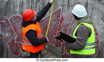 Builders with a tape measure