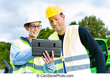 builders with blueprint on construction site