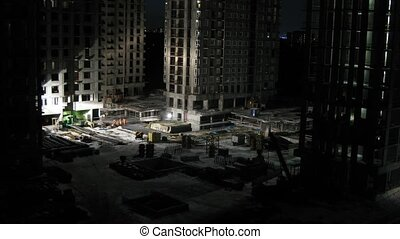 Builders work on construction site at night, time lapse