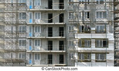 Builders work on exteriors of the building