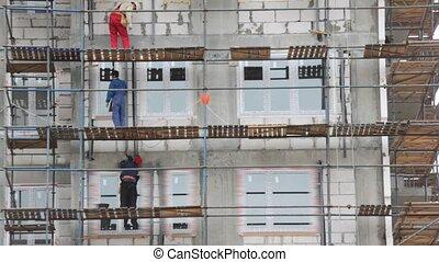 builders works on falsework in building area
